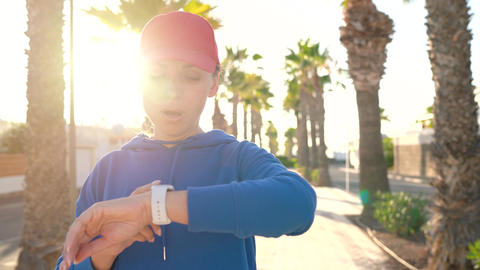 Woman stops while jogging to check the data in the smart watch application Live Action