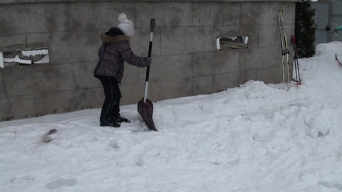 The girl with a shovel removes snow Stock Video Footage