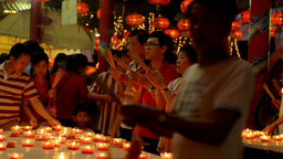 Thai Family Praying by Candlelight at a Temple During Chinese New Year Footage