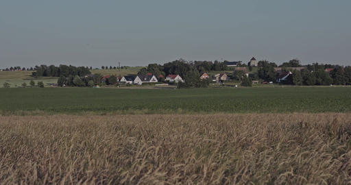 A grassy field at the countryside and a village in the background Footage