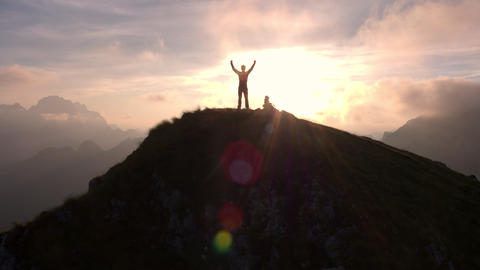 Aerial - Silhouette of a man standing on top of the mountain with arms raised Footage