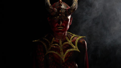 Evil demon woman with horns and red eyes is sitting in the smoke, slow motion Live Action