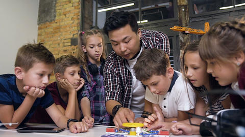 Creative children with teacher launching electronic constructor with fan and Live Action