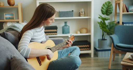 Slow motion of attractive girl enjoying music playing guitar in apartment alone Footage