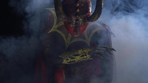 Scary red female demon with long horns and red eyes, with an evil look Live Action