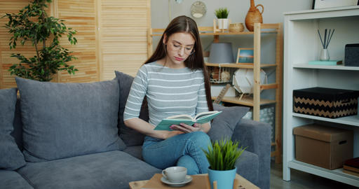 Portrait of serious lady reading book on sofa in apartment focused on activity Footage