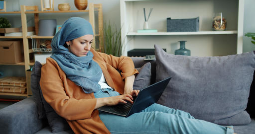 Independent Muslim girl working with laptop in apartment typing busy with work Footage