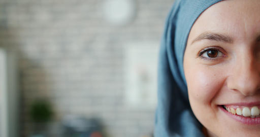 Slow motion of beautiful mixed race lady in hijab half face on brick background Live Action