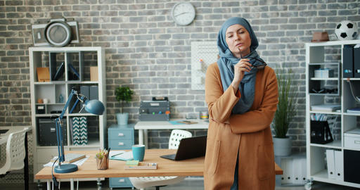 Female Muslim office worker in hijab standing in workplace holding glasses Footage