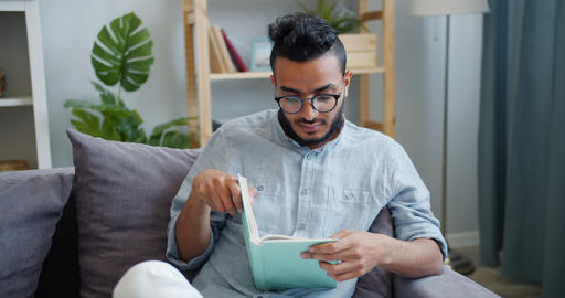 Attractive African American man reading interesting book at home alone Footage