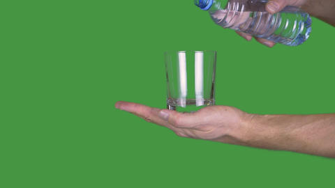 Male hand holding empty glass on green background. Man pouring water from Live Action
