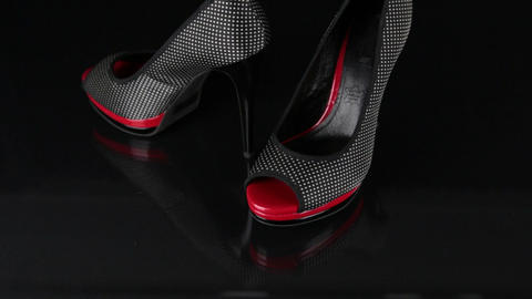 Approaching, a pair of black shoes standing on a black background. Fashion Footage