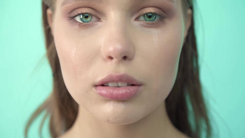 Face of young woman with tear drop close up. Crying Girl. Beautiful Woman Cry Footage