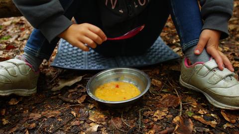 Camping lunch concept. Child eats porridge Live Action