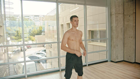 An athletic man training in the studio - repeats movements with a skipping rope Footage