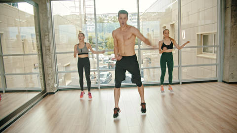 Fitness training in the studio - two young women training with their coach - Live Action