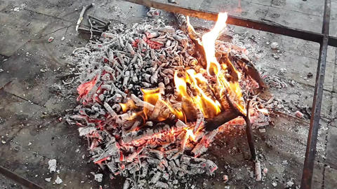 Hot embers that are being consumed, with small flames Live Action