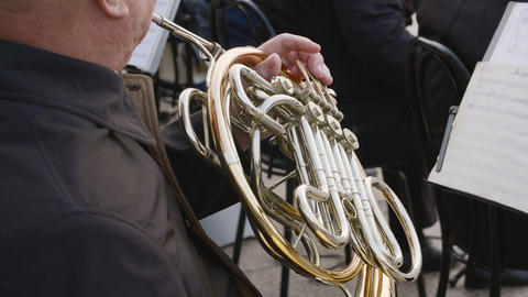 Close up man playing on french horn on city street. Street musician play music Live Action