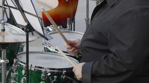 Drummer plays music on drums kit outdoor. Close up drummer hand with drumstick Live Action