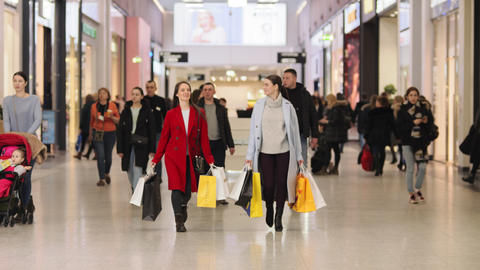 girls shoppers with purchases walk along shopping mall Live Action