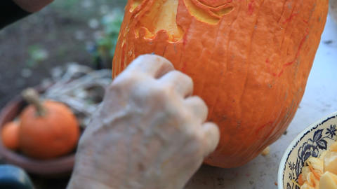 Closeup man carves Halloween pumpkin Footage
