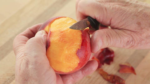 Senior man peeling a juicy peach Footage