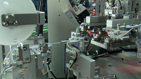 Close up on industrial production line for small parts, robotic arms Footage