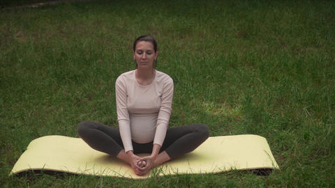A pregnant woman practices yoga in the park on a rug, doing the asd baddha Live Action