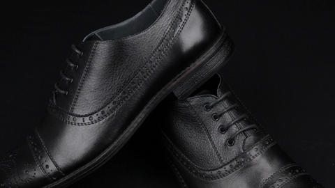 Approaching, pair of black classic men's shoes standing on on a black background Footage
