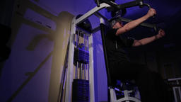 a young man is doing an exercise on the chest muscles on the simulator.copy Live Action