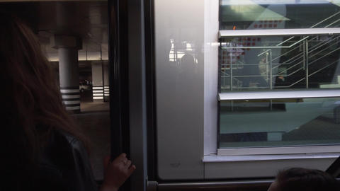 Two women with long hair are standing next to entrance doors in moving bus Live Action