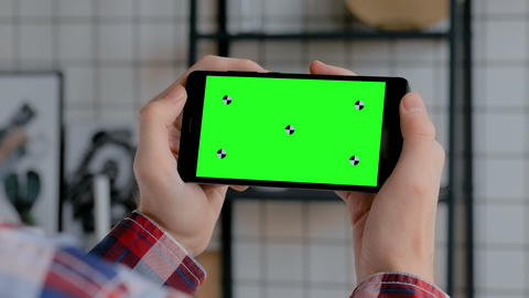 Man holding black smartphone with blank green screen - chroma key concept Footage