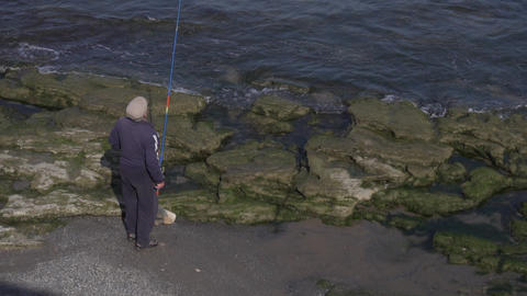 Old man in cap is fishing, standing on edge of rock shore close to water Live Action