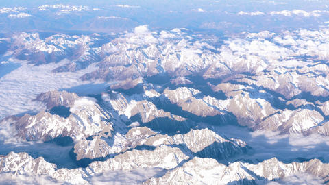 Beautiful view through airplane window, airplane flying above mountains with Live Action