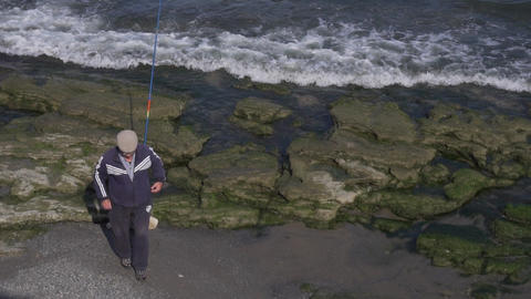 Old man in cap is walking away of edge of sea shore where he left fishing rod Live Action