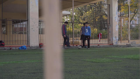 Bunch of boys are playing football on mini football pitch with high fences Live Action
