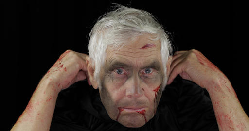 Old executioner Halloween makeup and costume. Elderly man with blood on his face Live Action
