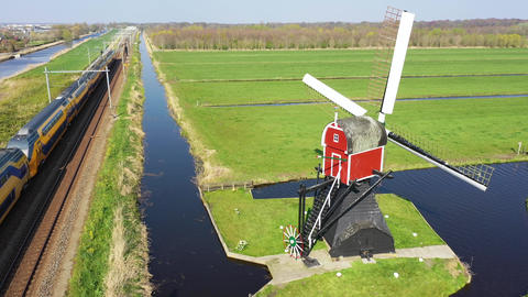Aerial view of high speed train passing by traditional Dutch windmill Live Action