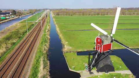 Aerial view of high speed train passing by traditional Dutch windmill Footage