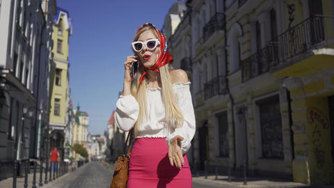 Beautiful young woman standing on the street talking by cellphone. Attractive Live Action
