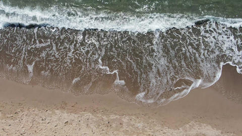 AERIAL: The surf with foam is trying to get ashore to wash away the traces that Live Action