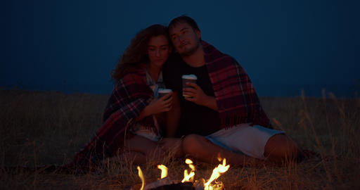 Romantic couple sitting around a campfire at night Footage
