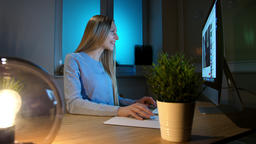 Smiling woman working on computer at night. Smiling female in checkered shirt Footage
