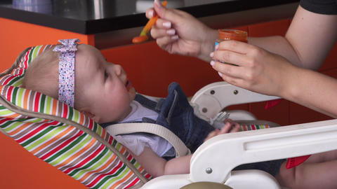 Mother feeds adorable baby girl Live Action