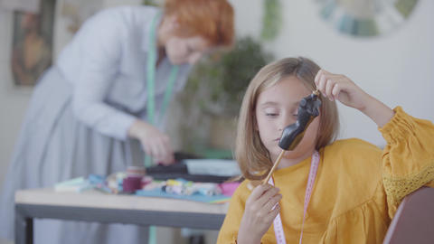 Little sad daughter examines little dummy while her busy red-haired mother sews Footage