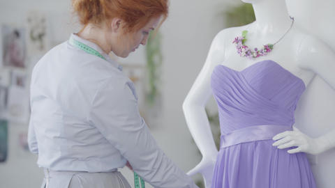 Woman corrects elegant violet dress that hanging on a mannequin in the room Footage