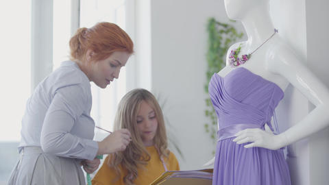 Beautiful red-haired woman measuring elegant violet dress that hanging on a Footage