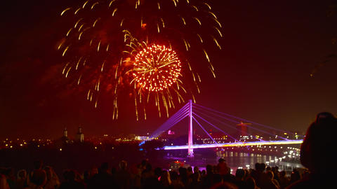 Crowd people watching festive fireworks over illuminated bridge in night city Footage