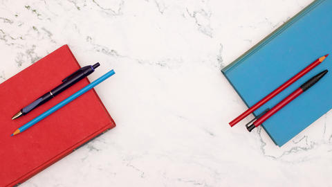 Stop motion animation of appearing blue and red books with blue and red pencils Animation