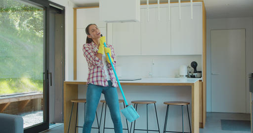 Beautiful young woman in protective gloves is singing using a mop and dancing Footage